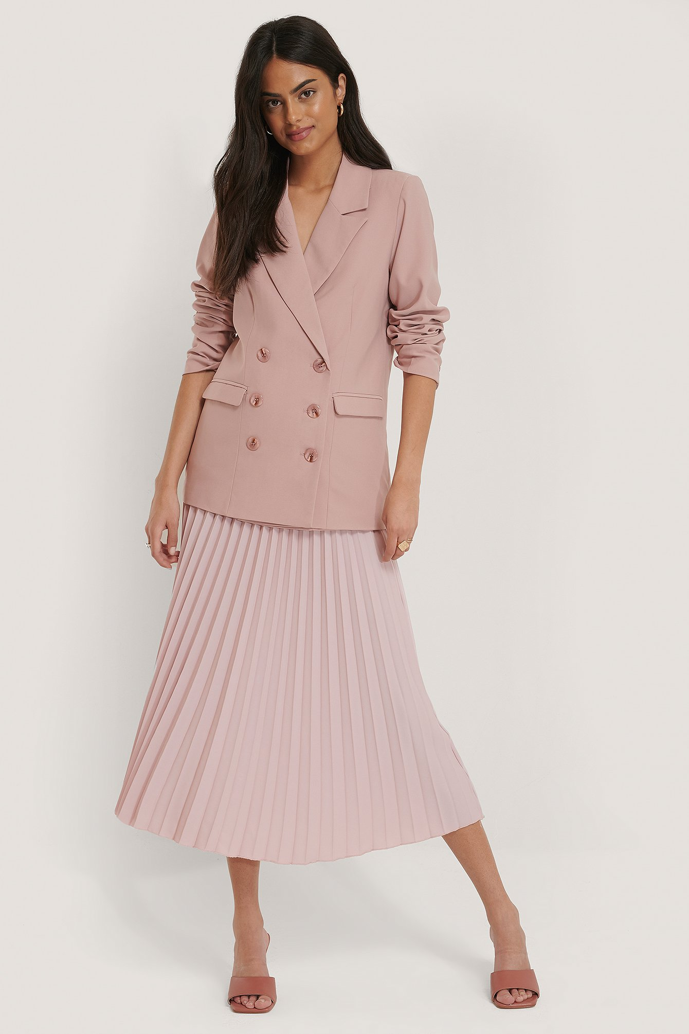 pink blazer and pink pleated skirt are pleated skirts in style